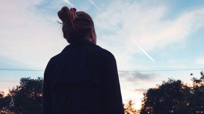 The silhouette of a young woman looking at sunset