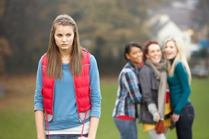 Upset ADHD Teenage Girl With Friends Gossiping In Background